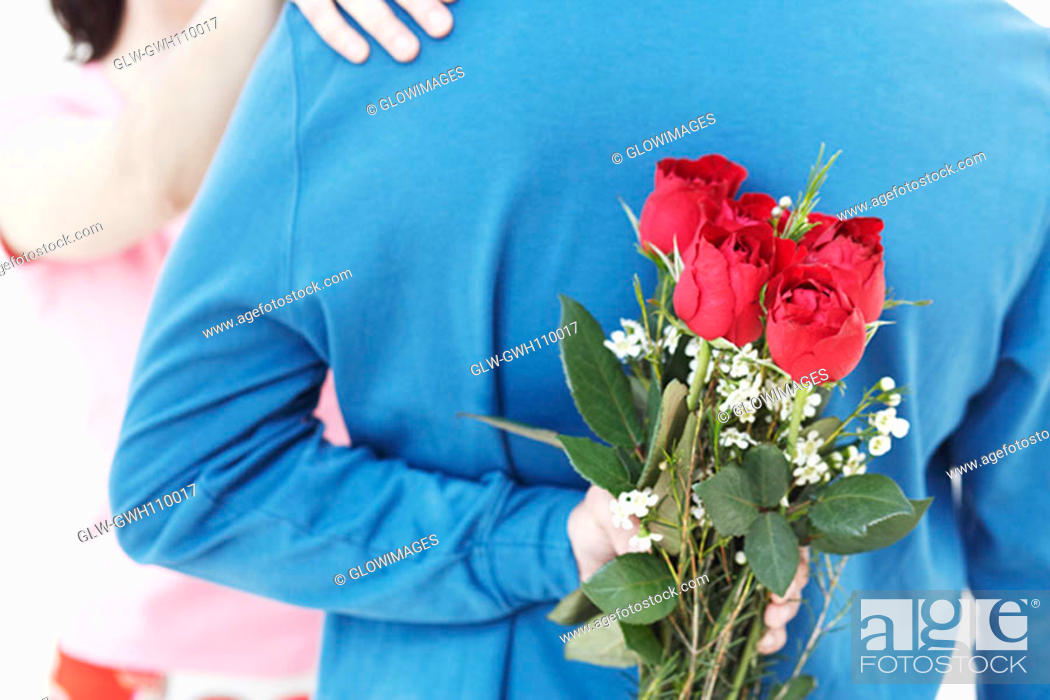Stock Photo: Rear view of a young man hiding a bunch of roses behind his back.