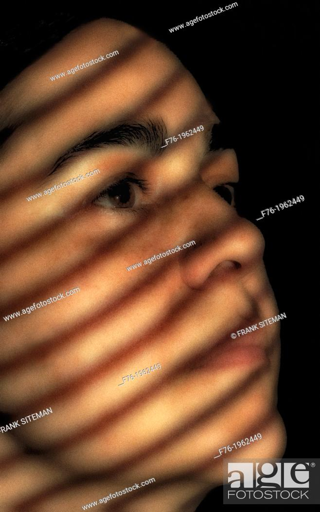 Stock Photo: Portrait of iranian woman with shadows from venetian blinds across her face.