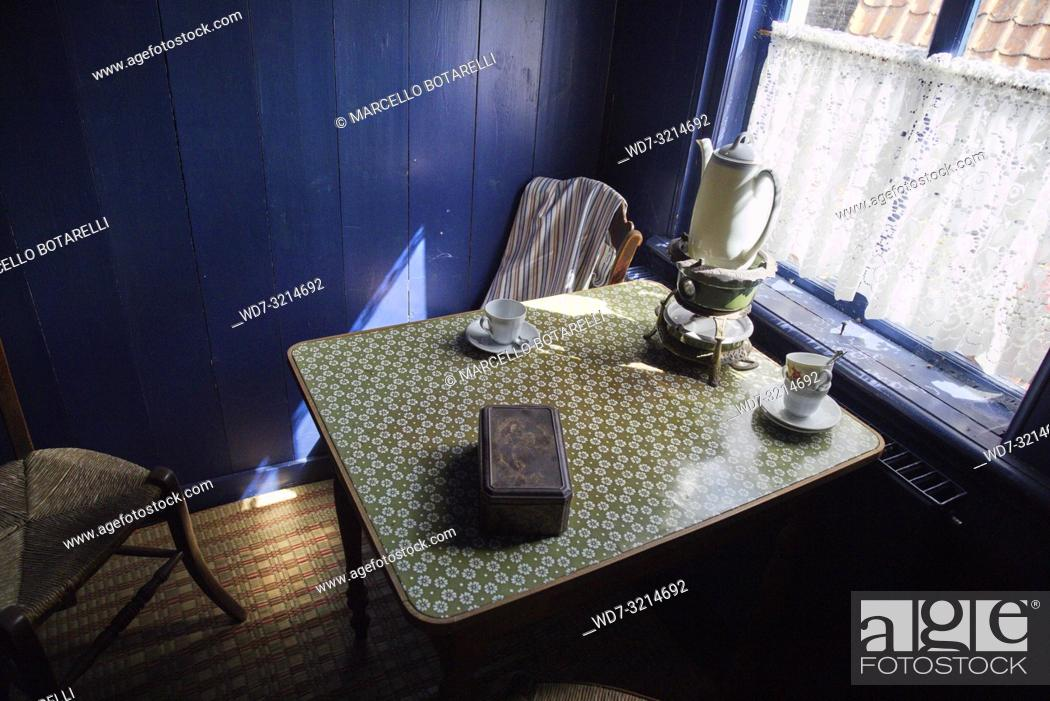 Stock Photo: Table with tea cups, in a small room with a blue wall of a fishing village house in Enkhuizen, norther Holland.