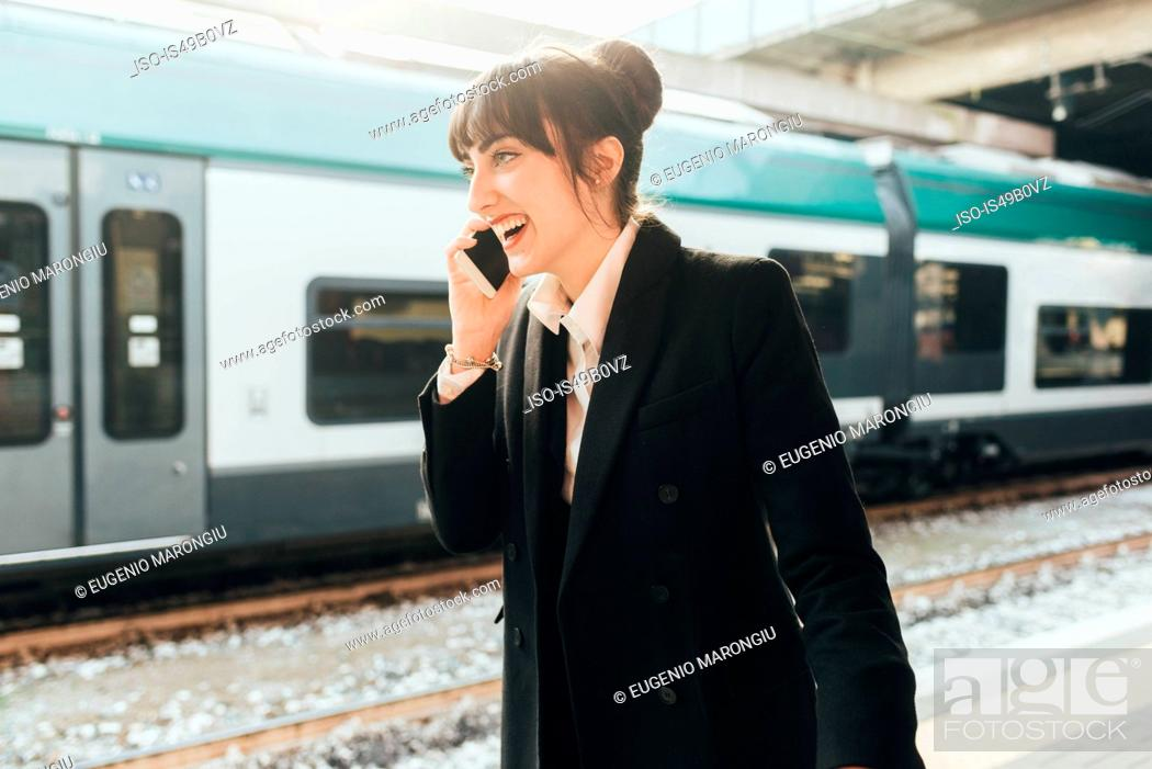 Stock Photo: Businesswoman using mobile phone in train station, Milan, Italy.