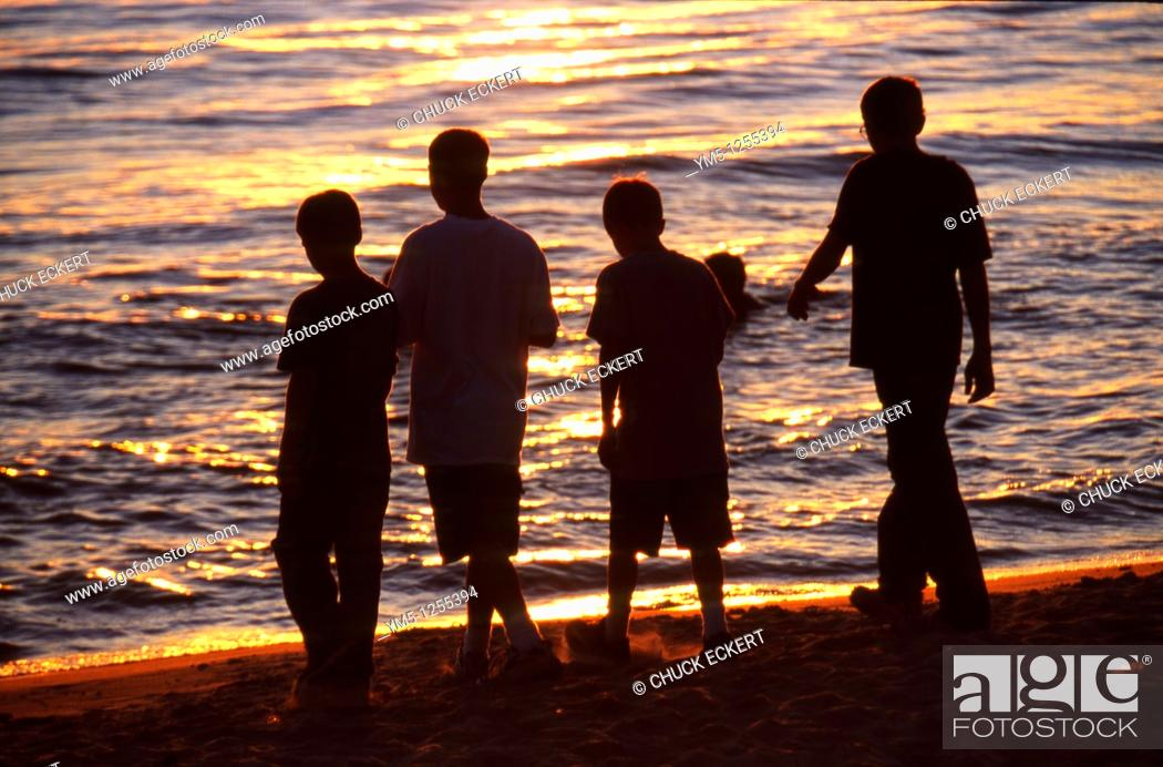 Stock Photo: Group of Teenage boys walking across beach to water.