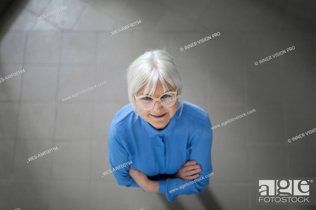 Stock Photo: Smiling senior businesswoman looking up on office hallway.