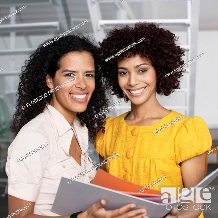 Stock Photo: Two businesswomen in office space holding folder.
