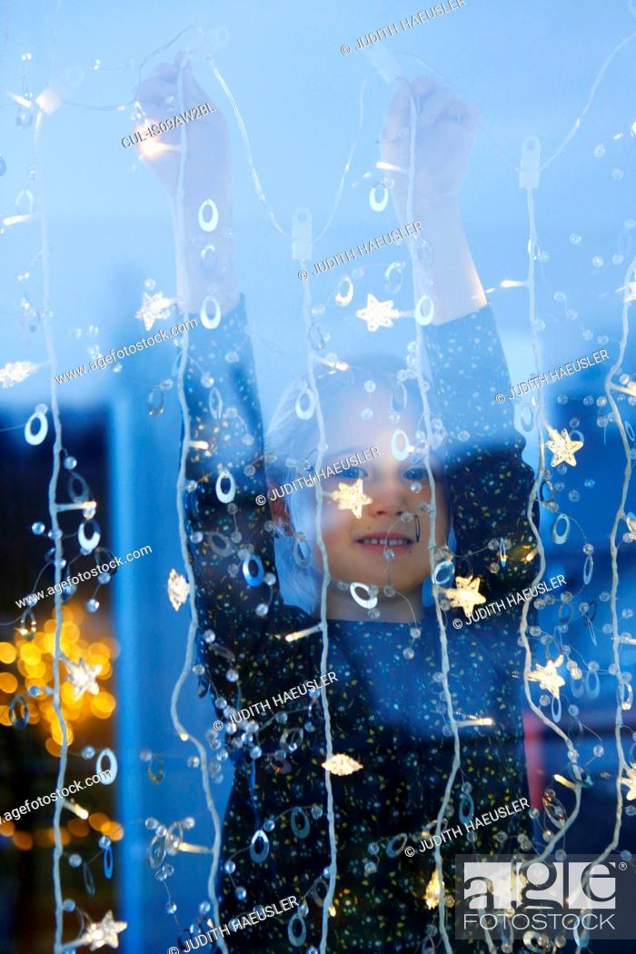 Stock Photo: View through window of girl arms raised hanging decorative lights, looking at camera smiling.