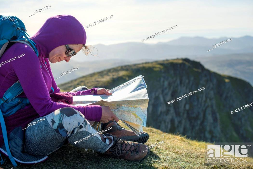 Stock Photo: Checking a map on the way down from Helvellyn towards Grisedale Tarn in the English Lake District, Lake District National Park, Cumbria, England, United Kingdom.