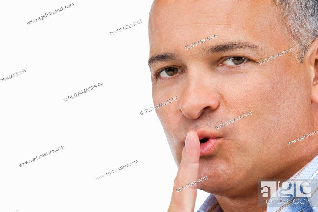 Stock Photo: Portrait of a mature man gesturing with his finger on his lips.