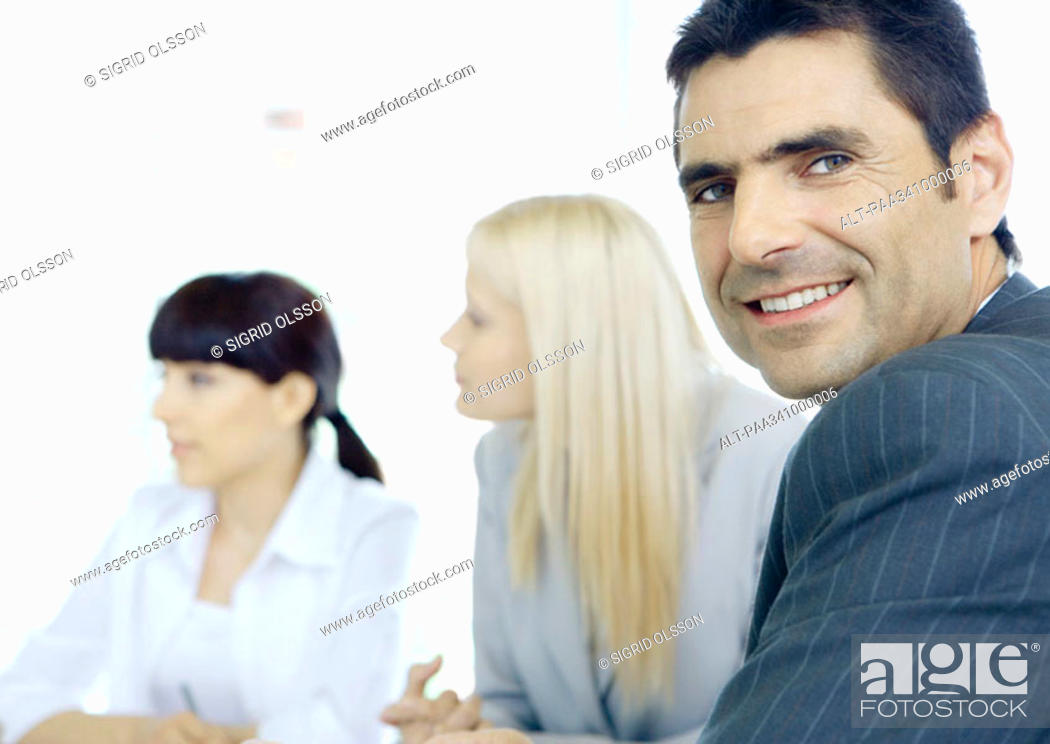 Stock Photo: Businessman in meeting, smiling at camera.