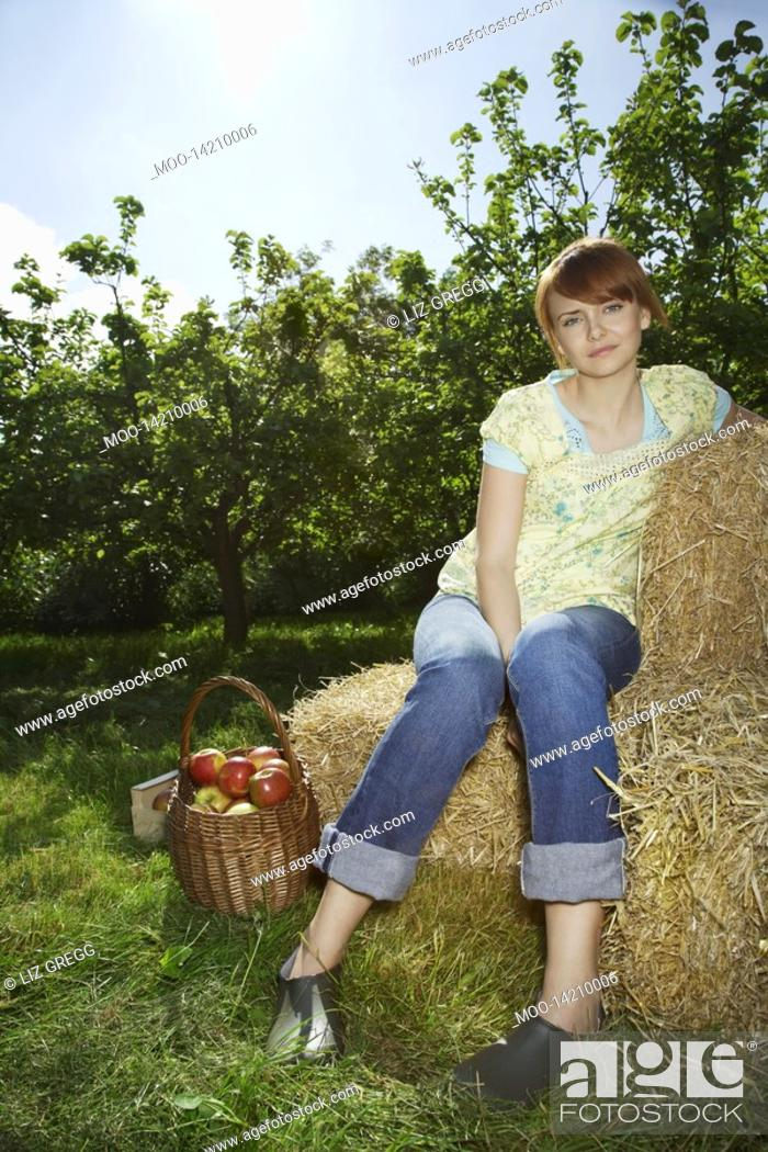 Stock Photo: Woman sitting on hay bales near orchard portrait.