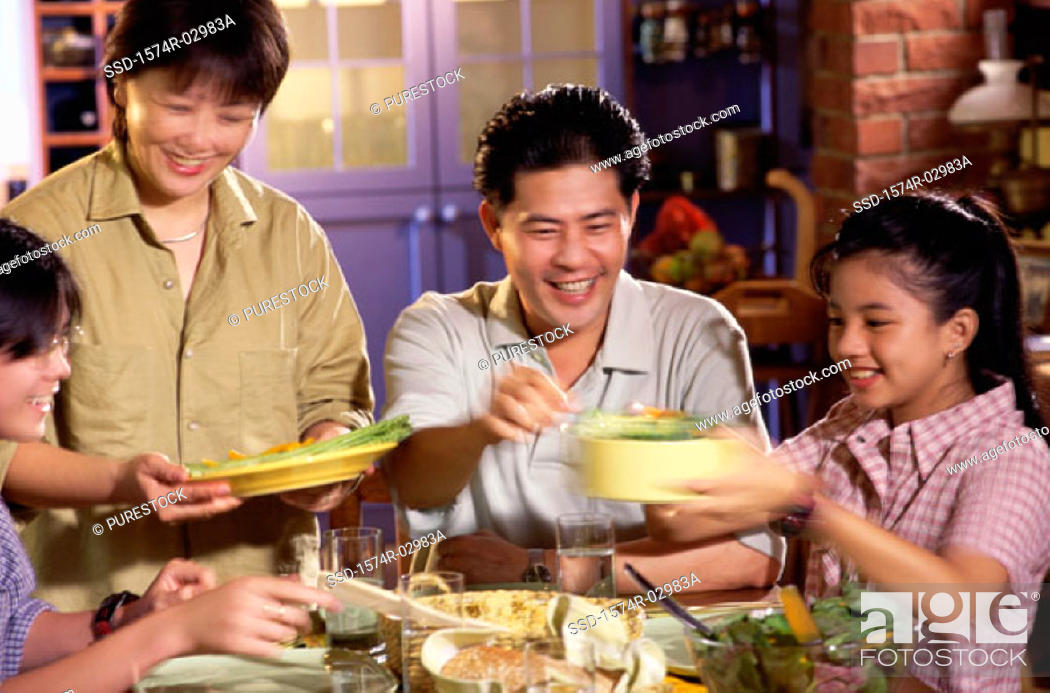 Stock Photo: Parents with their children at a dining table.