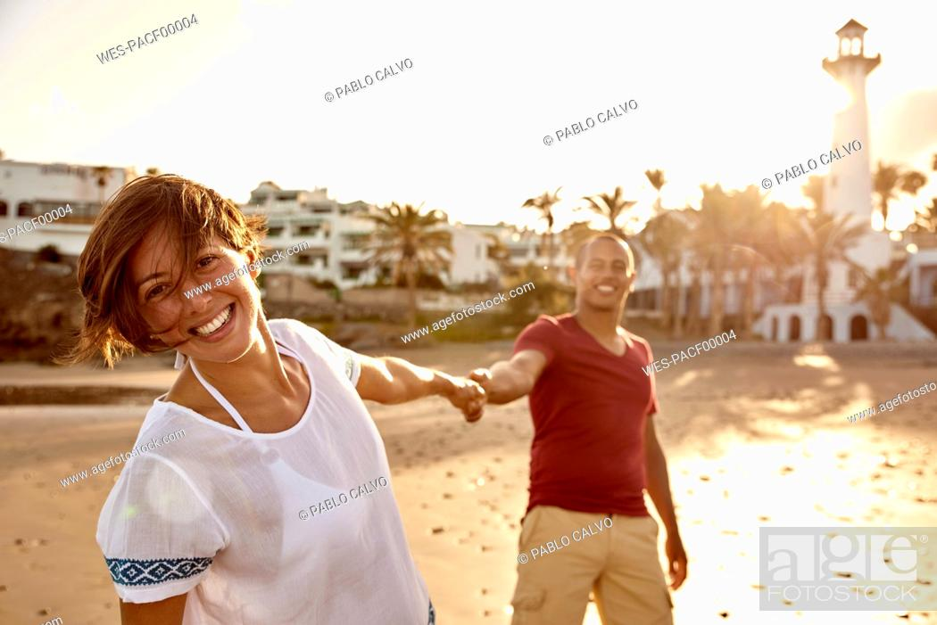 Stock Photo: Spain, Canary Islands, Gran Canaria, portrait of happy woman holding hand on the beach.