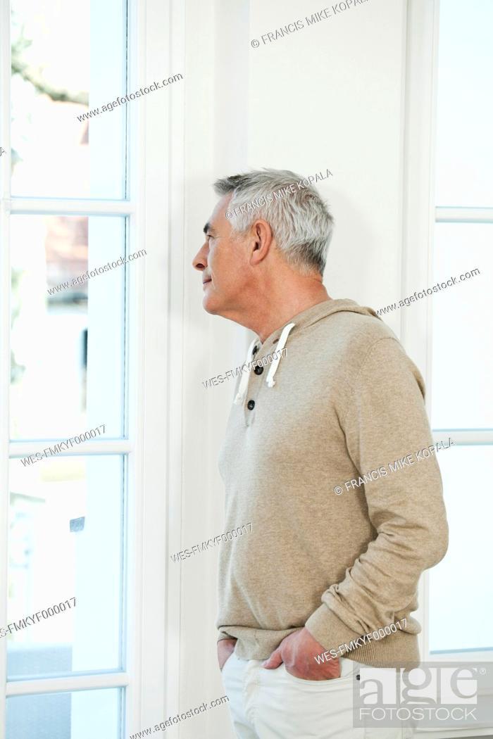 Stock Photo: Germany, Berlin, Senior man looking through window.