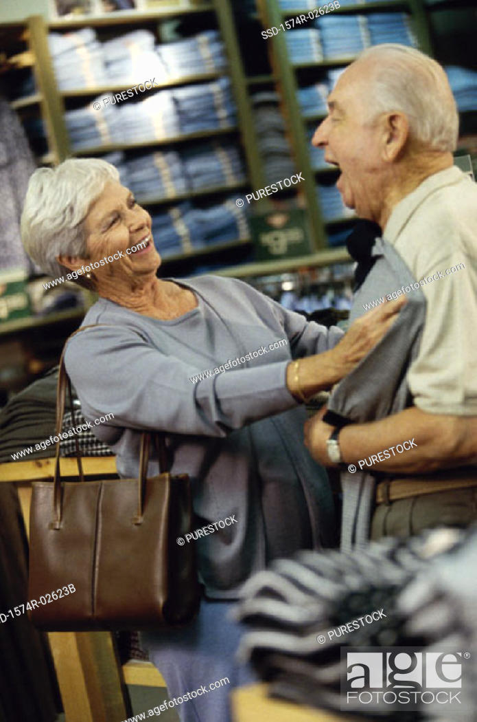 Stock Photo: Senior woman holding a t-shirt against a senior man in a clothing store.
