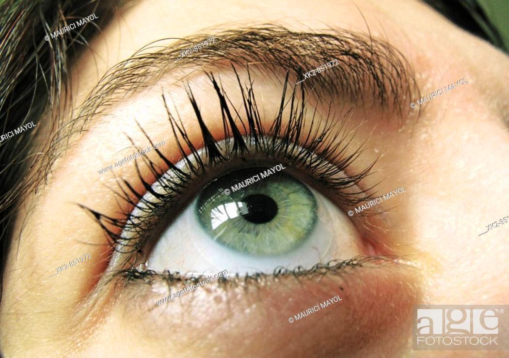 Stock Photo: Detalle de un ojo verde con pestañas maquilladas con rimmel.