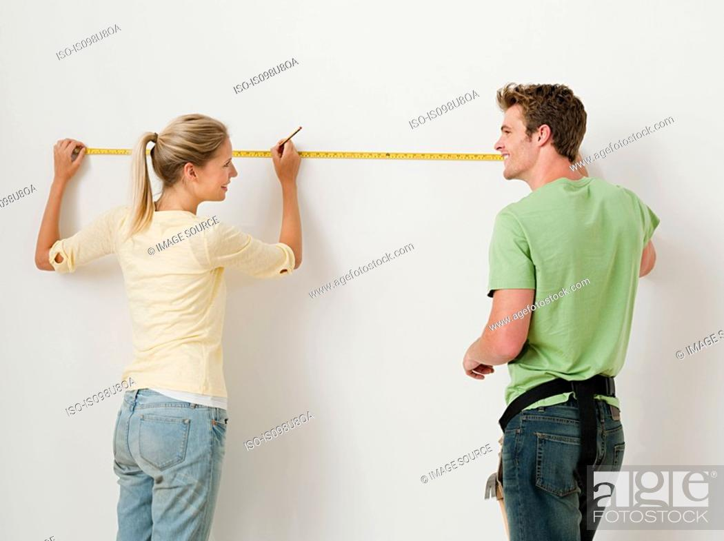 Stock Photo: Young couple using measuring tape on wall.
