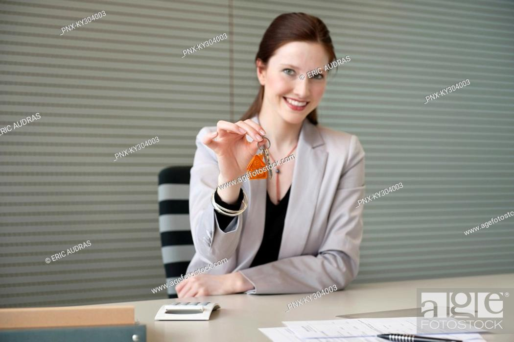 Stock Photo: Female real estate agent holding house keys in an office.