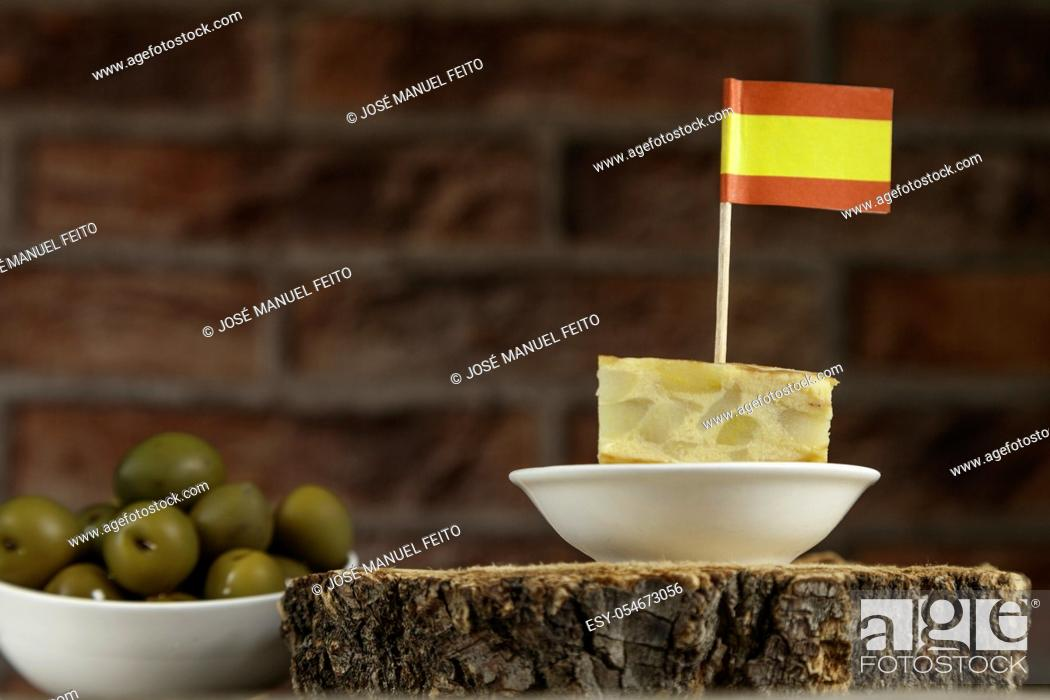 Stock Photo: Spanish omelette brochette with spanish flag and olives bowl from below on red brick background.