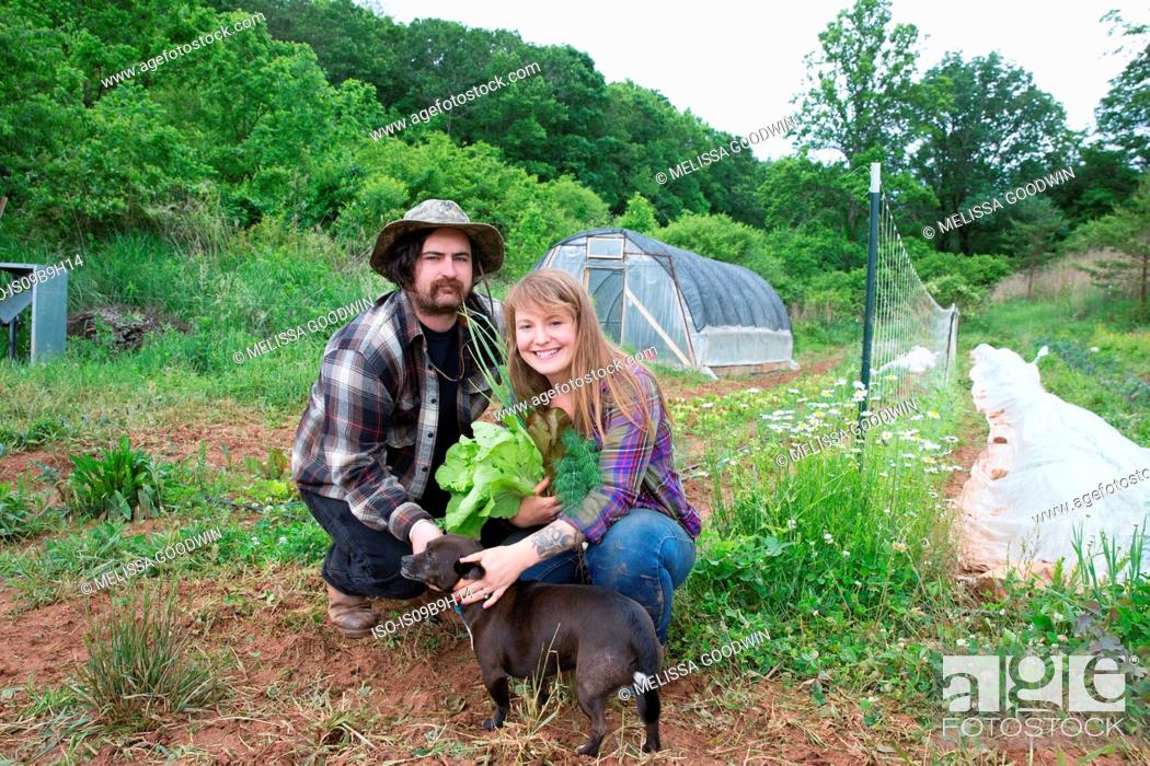Stock Photo: Couple with dog in vegetable garden looking at camera smiling.
