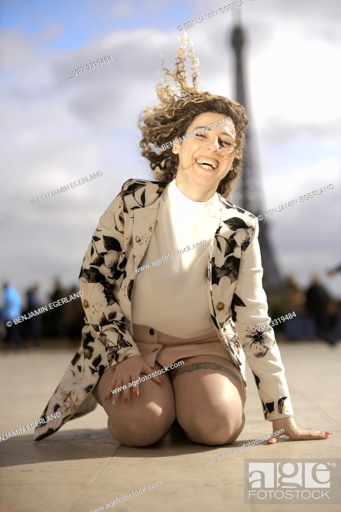 Stock Photo: woman kneeling outdoors in public in city next to tourist sight Eiffel Tower, at Espl. du Trocadéro, in Paris, France.
