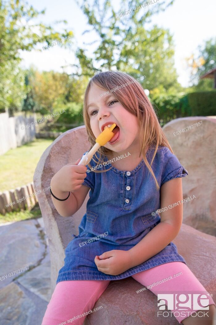Stock Photo: four years old blonde girl with blue denim dress sitting in public park, biting orange or yellow ice lolly or popsicle.