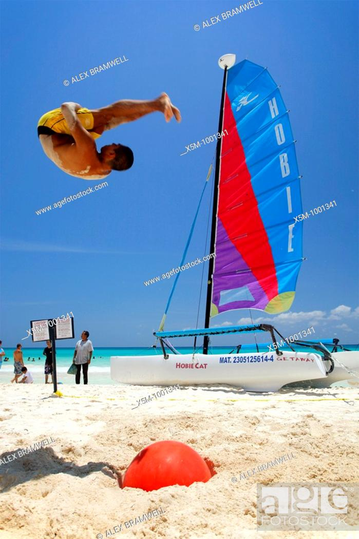 Stock Photo: Man doing a somersault on Playa del Carmen Beach in the Mexican Caribbean.