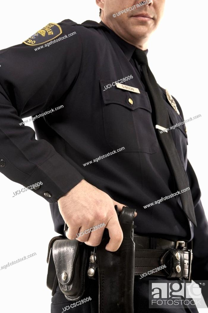 Stock Photo: Male police officer reaching for his holster.
