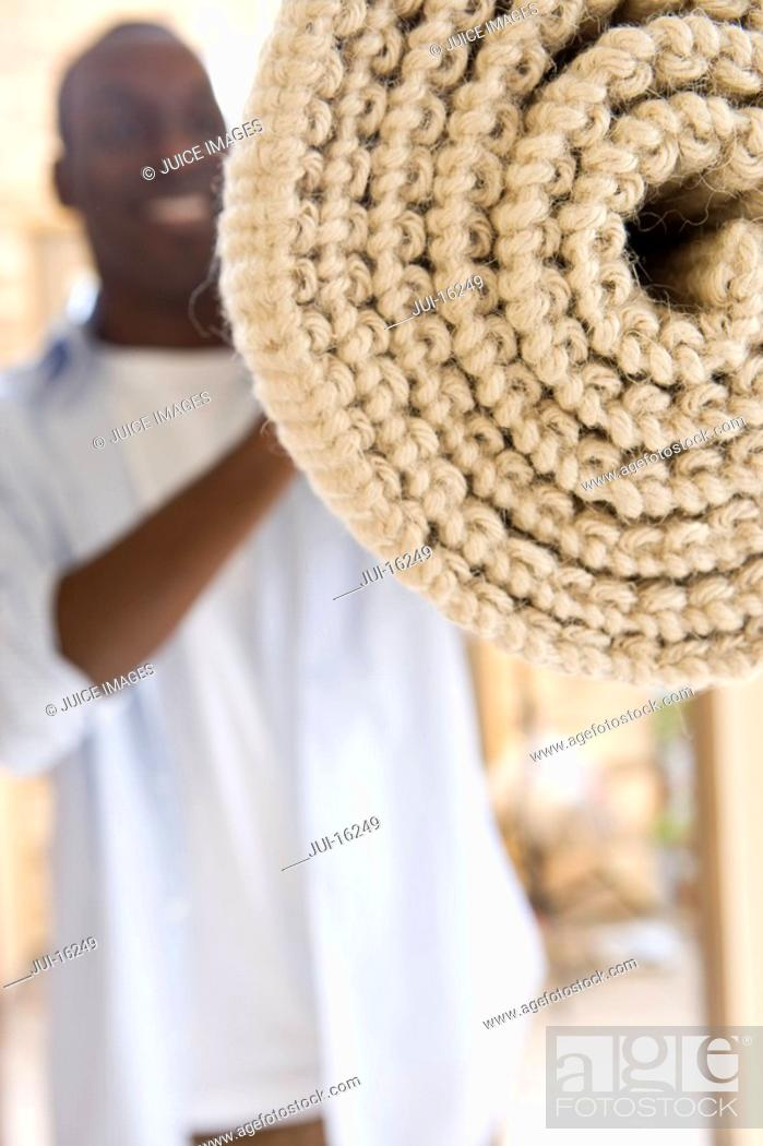 Stock Photo: Man moving rolled carpet.