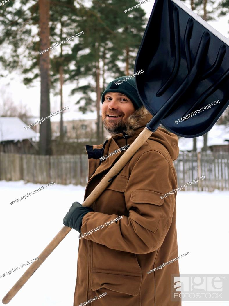 Stock Photo: Portrait of smiling man with snow shovel.
