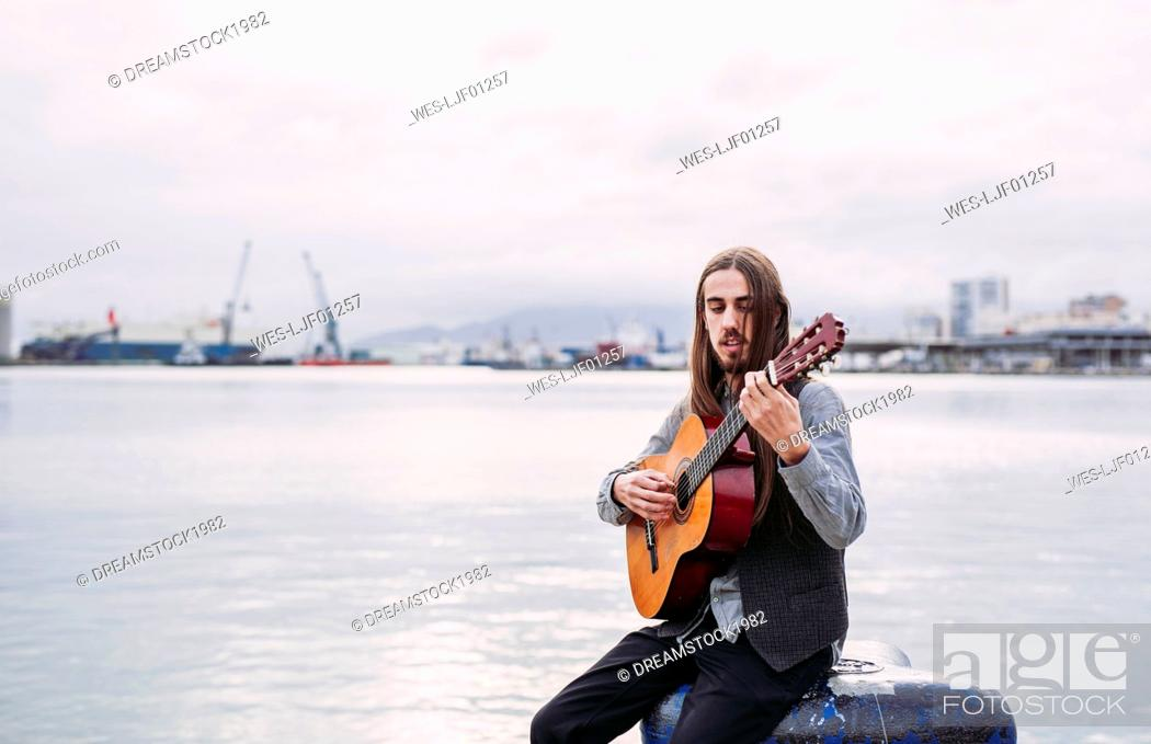 Stock Photo: Young musician playing guitar at the port.
