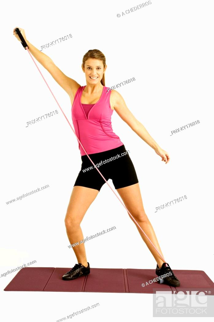 Stock Photo: Portrait of a young woman exercising with a resistance band.