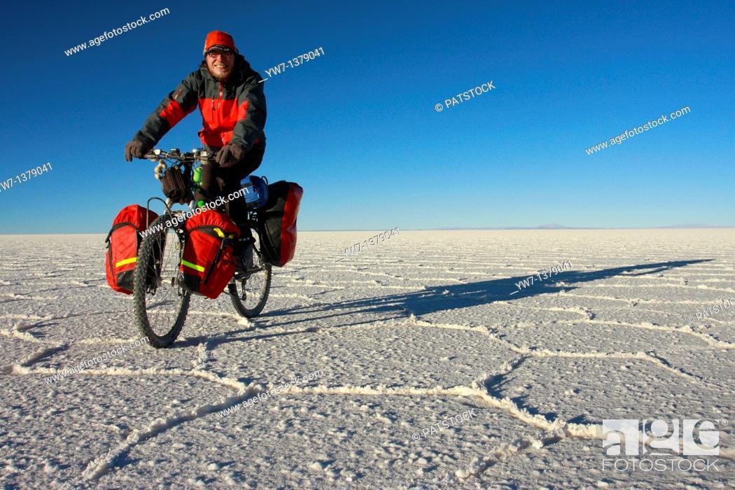 Stock Photo: A biker is cycling through the frozen salt lake called 'Salar de Uyuni' in Bolivia.