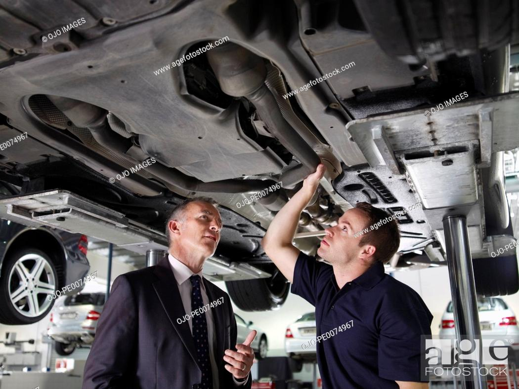 Stock Photo: Businessman looking underneath car with mechanic.