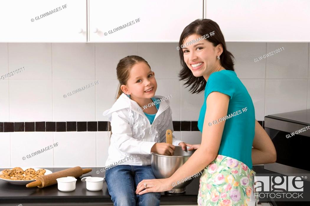 Stock Photo: Young woman making cookies with her daughter in the kitchen.