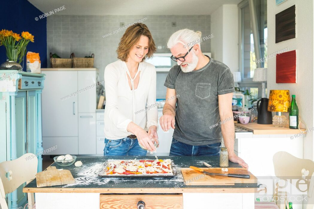 Stock Photo: Mature couple preparing a pizza in kitchen at home.