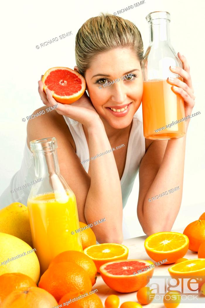 Stock Photo: portrait of young woman with citrus fruit and orange juice.