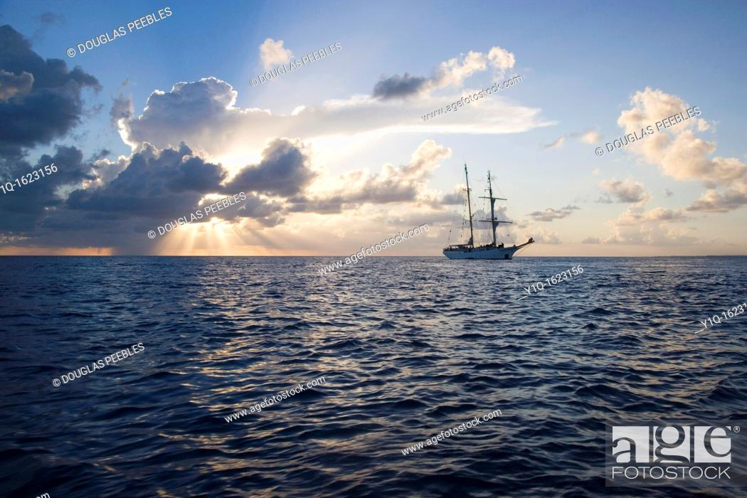 Stock Photo: Sunset with Sailboat, South Pacific.