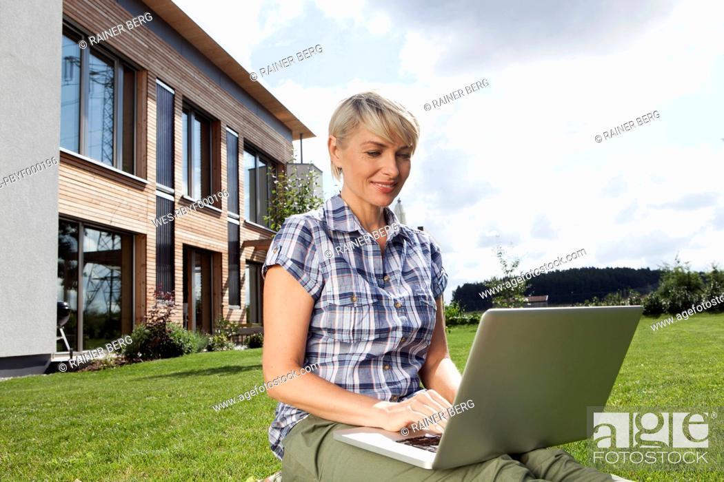 Stock Photo: Germany, Bavaria, Nuremberg, Mature woman using laptop in garden.