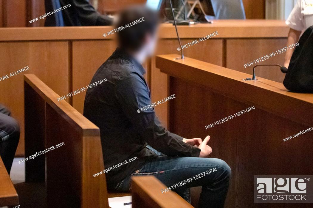 Stock Photo: 05 December 2019, Bavaria, Nuremberg: At the beginning of the trial, a 22-year-old (l) waits sitting on the bench in the courtroom of the Regional Court.