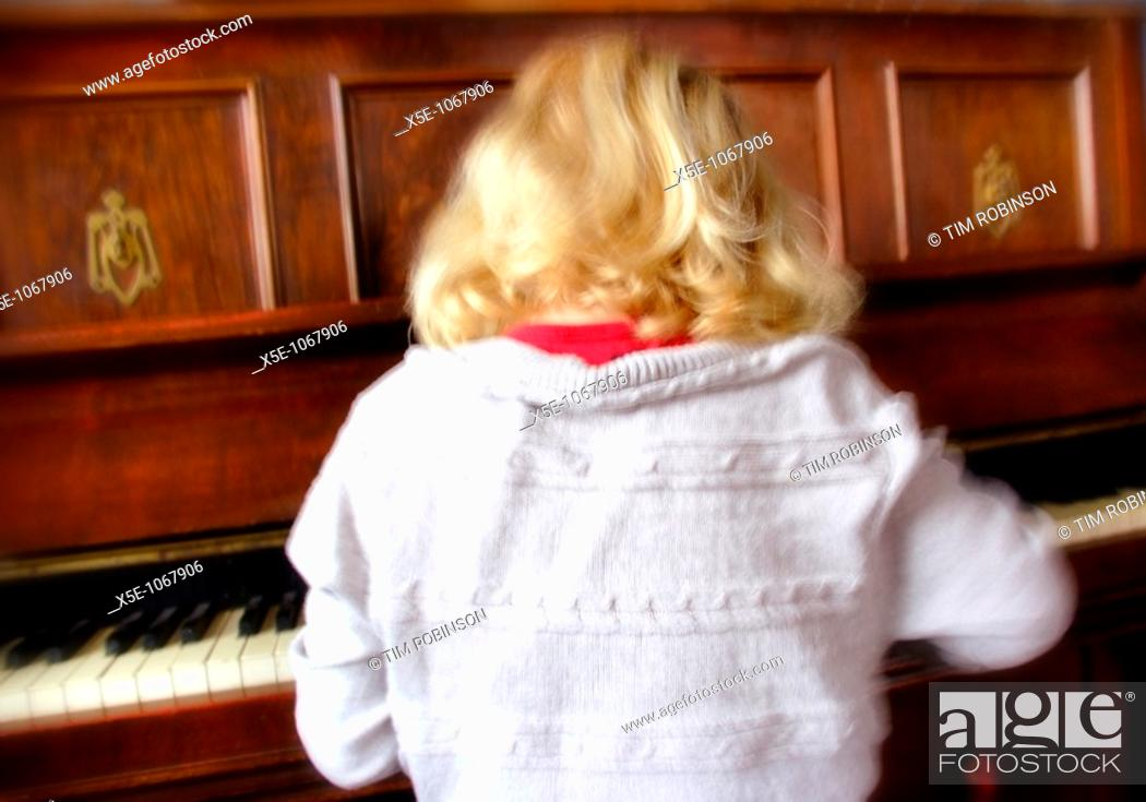 Stock Photo: Rearview 7 year blonde girl playing piano, motion blurred.