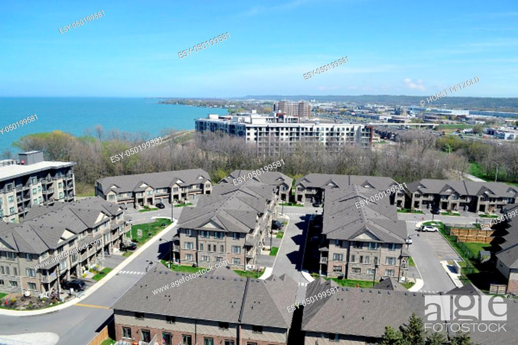 Stock Photo: An aria view of some big development with new houses and condo.buildings on the shore of lake Ontario on a sunny spring day.