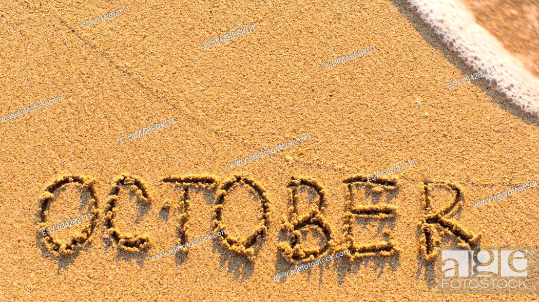 Stock Photo: Inscription OCTOBER on a gentle beach sand with the soft wave (months of the year series).