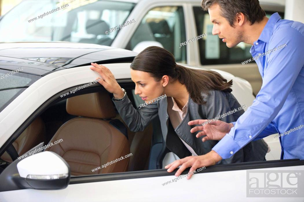 Stock Photo: Couple examining a car before buying.