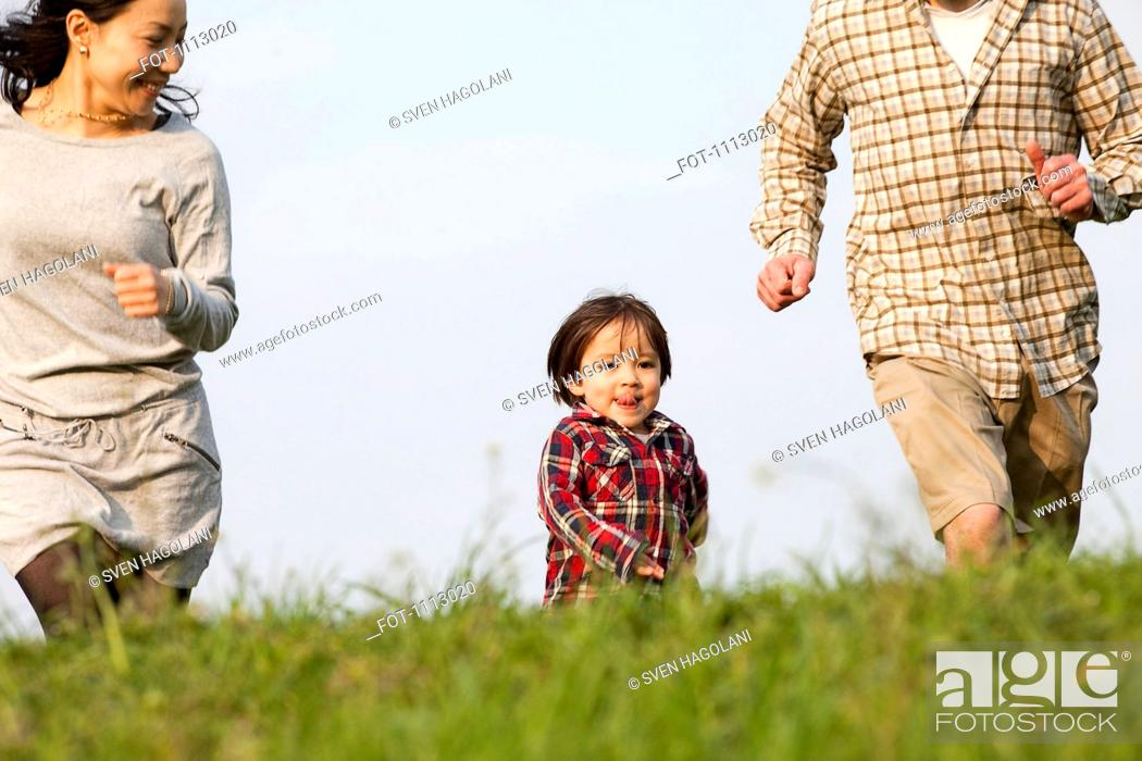 Stock Photo: A young boy running in the park in between his mother and father.