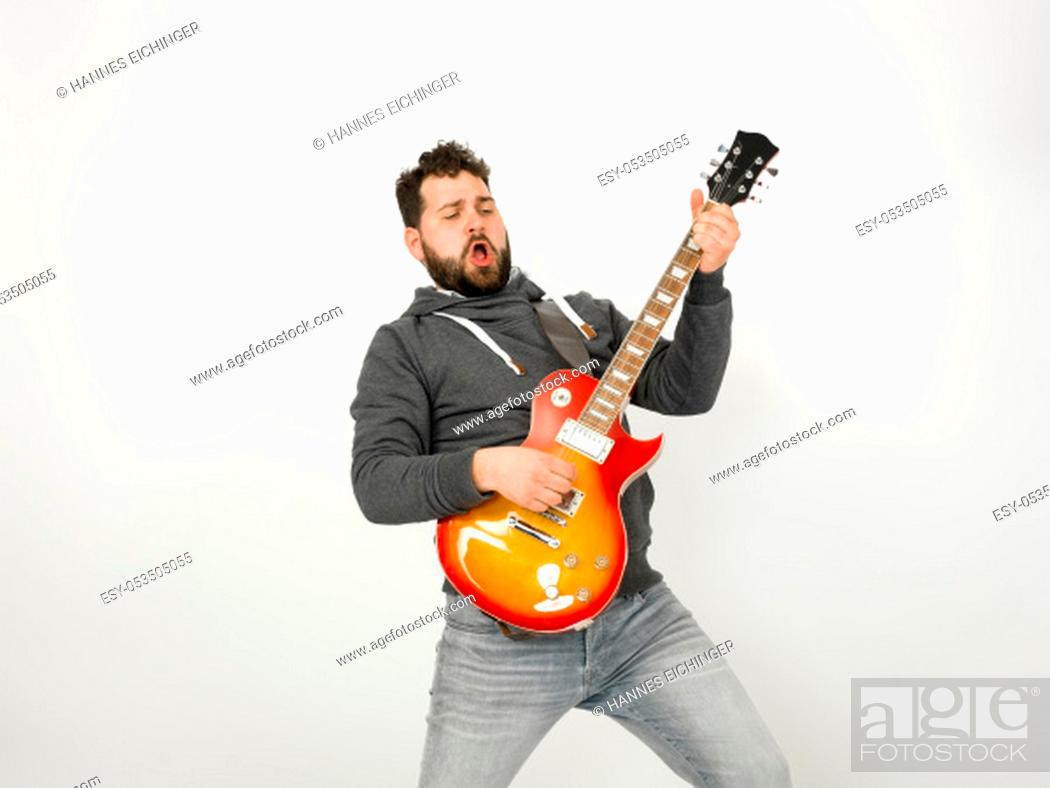 Stock Photo: cool man with black hair and beard, wearing grey hoodie playing the electric guitar in front of a white background.
