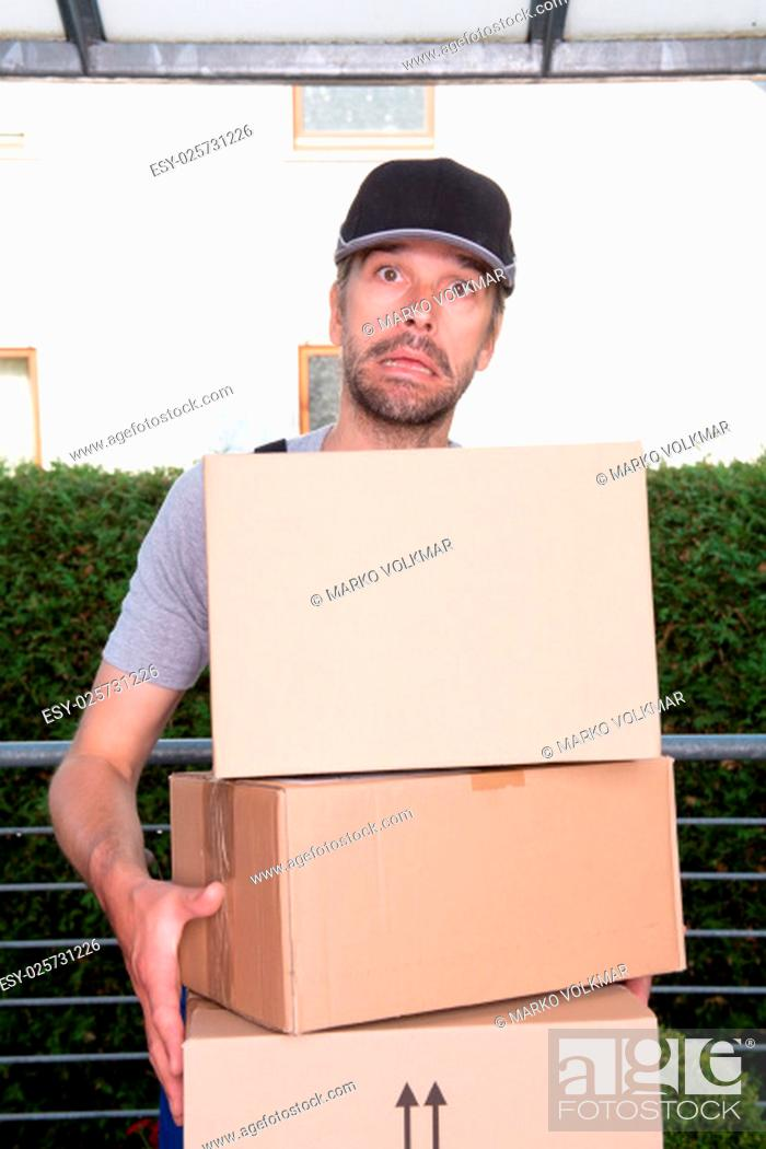 Stock Photo: overstrained postman with parcels and dark cap.