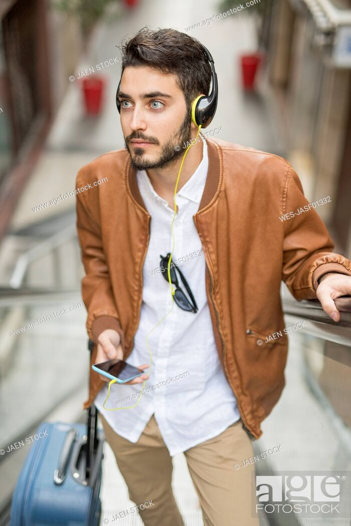 Stock Photo: Man with cell phone, headphones and suitcase on escalator.