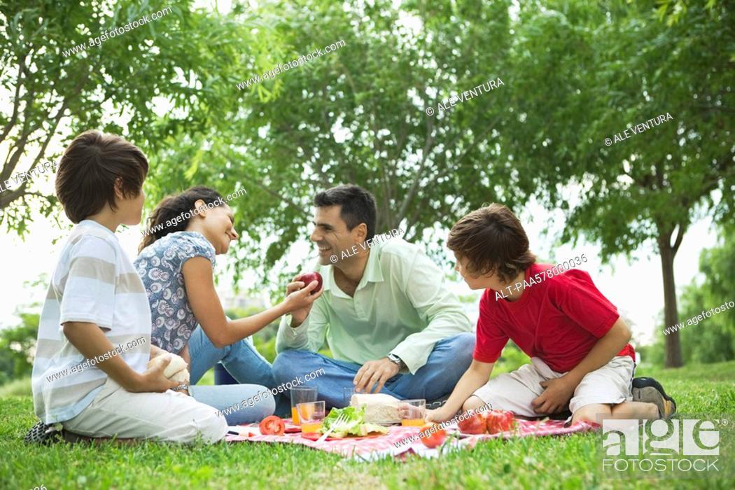 Stock Photo: Family enjoying picnic outdoors.