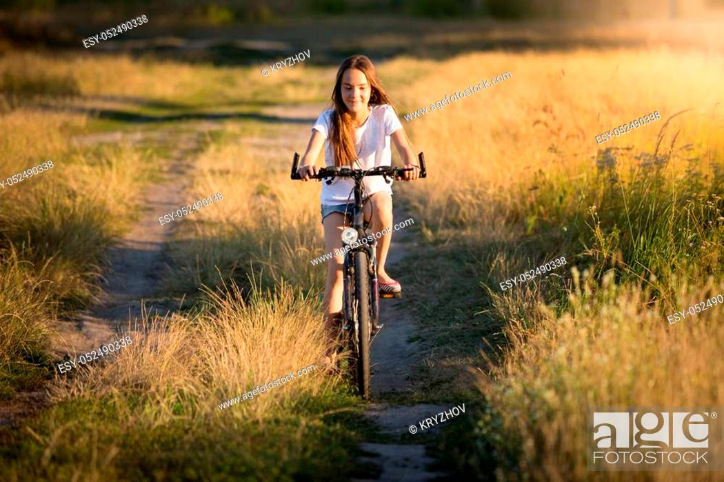 Stock Photo: Beautiful smiling girl riding on bicycle in meadows at sunset.