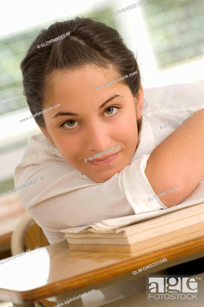 Stock Photo: Portrait of a teenage girl leaning on a textbook.