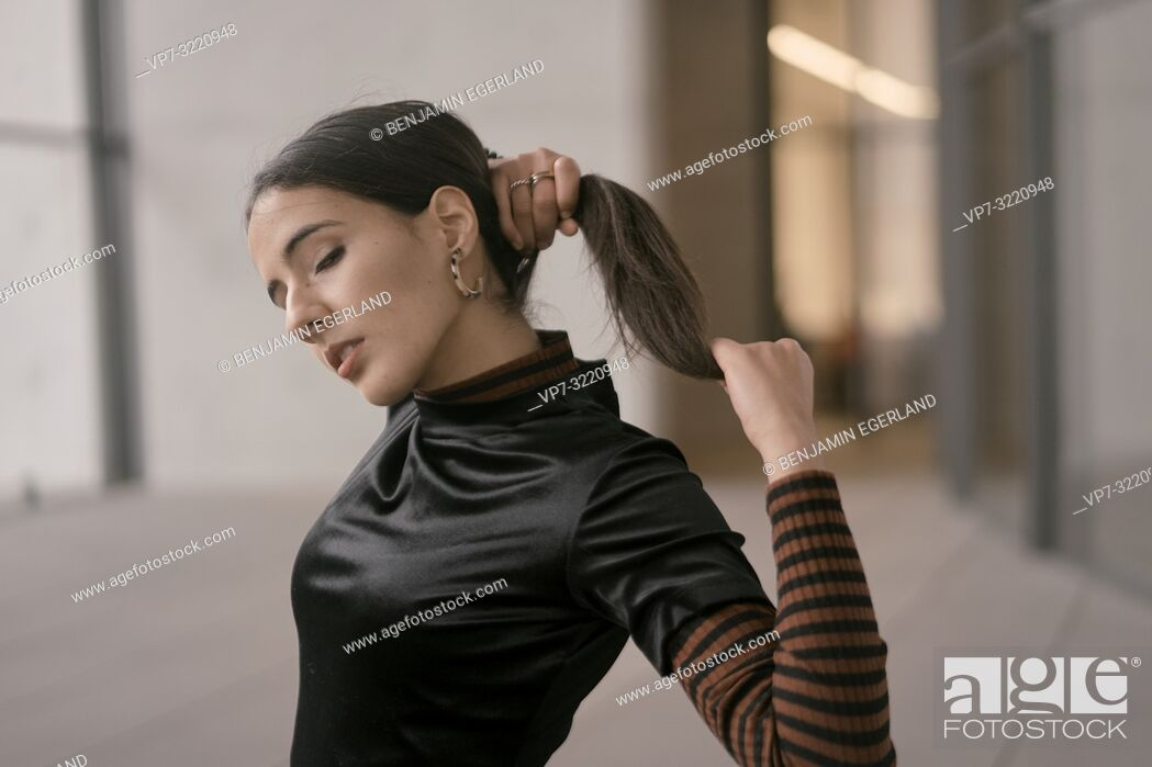 Stock Photo: portrait of sensitive fashionable woman with closed eyes, indoors, making pigtail, pensive thoughtful feelings, in Munich, Germany.