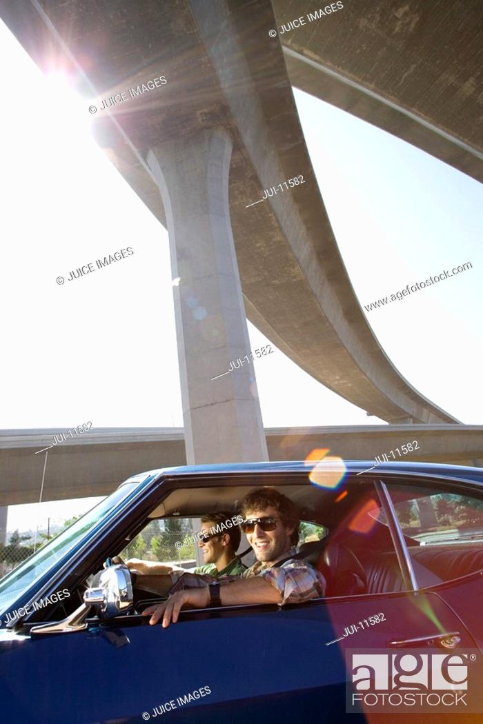 Stock Photo: Two young men wearing sunglasses in car beneath overpass, smiling lens flare.